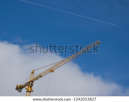 View for Working yellow construction crane against blue sky and the plane in the background
