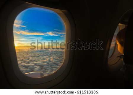 View form airplane window with the child look outside on sunset with cloud. #611513186