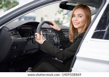 View form side of cheerful woman sitting in new white car in auto salon, looking at camera and smiling. Female customer choosing and testing automobiles in showroom. Concept of car presentation. #1409508869