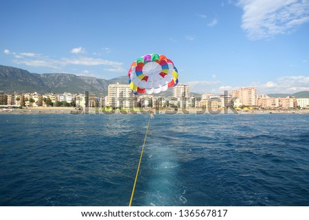 View from a boat to tied colored parachute with woman