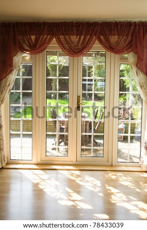 view from a empty room showing curtains and French uPVC patio doors with sun shining through and garden in the background