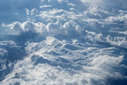 View from a great height through the clouds to the mountains and the earth, the movement of air masses. Concept: God's view of the earth, the view from the plane window.