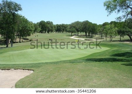 view from a green back down a tree lined fairway