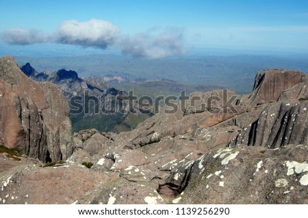 View from a mountain on a clear day with blue sky. Granite massif, valleys and couple of clouds. Taken from the top of Pic Boby (2nd tallest mountain in Madagascar).