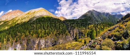 View from a mountain trail leading to the mountain pass in the Eastern Sayan. At the bottom and the center - a small mountain river canyon. Republic of Buryatia. panorama