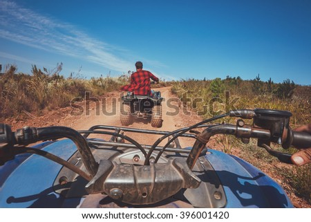 View from a quad bike in nature. Man in front driving off road on an all terrain vehicle. POV shot. Stock photo ©