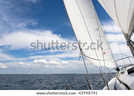 View from a sailing yacht, sailing in a nice breeze on a blue lake Grevelingen