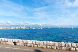 View from a seafront street on the French Riviera of the bay, sea and town of Antibes, France.
