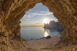 View from a small grotto on an evening sun setting behind the coastal cliffs. Crimea.