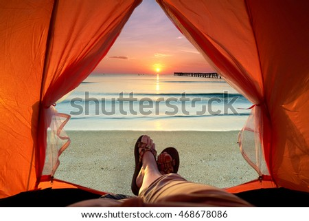 view from a tent on sunset at beach, human legs lying in tourist tent with view of the sea                               #468678086