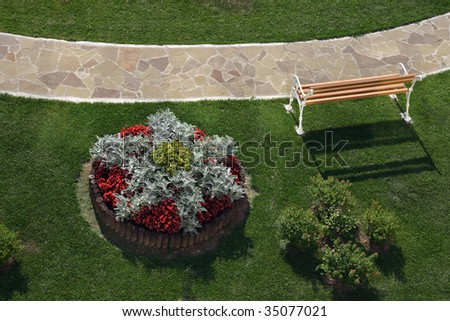 View from a terrace hotel on a park path,  bench, flowerbed and green lawn