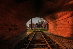 View from a tunnel. Historic train track in the park of Frankfurt on the river Ufer Main. Trees and meadow with flowers. Skyline of the financial district in the background