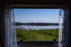 View from a window of camper to beautiful lake lanscape