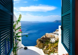 View from a window overlooking the sea, caldera and whitewashed village of Oia on the island of Santorini Greece.
