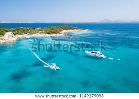 View from above, aerial picture of two boats sailing on a transparent and turquoise Mediterranean sea. Emerald Coast (Costa Smeralda) in Sardinia, Italy.