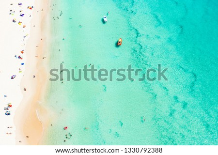 View from above, aerial view of a beautiful tropical beach with white sand, turquoise clear water and people sunbathing, Surin beach, Phuket, Thailand.