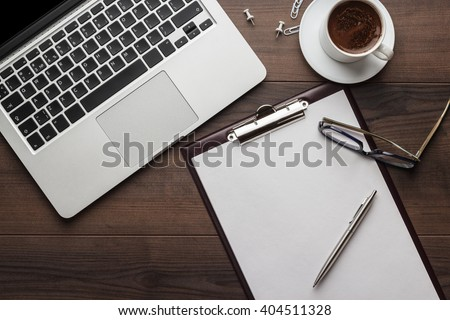 view from above. brown wooden office table with cup of coffee, notepad and laptop computer