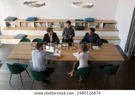 View from above diverse businesspeople negotiate in modern boardroom, staff take part in morning briefing or training lead by indian business coach, teamwork brainstorming, corporate education concept