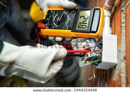 View from above. Electrician worker at work with the tester measures the voltage in a switch of a residential electrical system. Working safely with protective gloves. Construction industry. ストックフォト ©