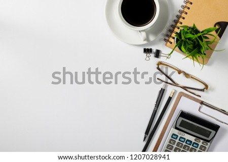 View from above.eye glasses,pen,notebook,calculator, and cup of coffee on white office desk with copy space.