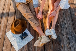view from above legs of couple traveling in summer dressed in sneakers, man and woman boho hipster style fashion having fun together, map, hat, photo camera, sightseeing, footwear fashion