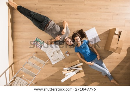 view from above, looking at the camera a young couple lying on the floor of their new home, there are blueprints to help them to think about their new interior decoration