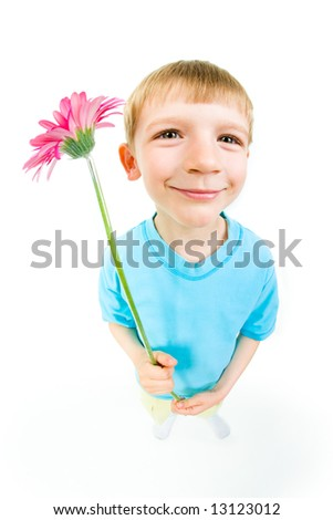 View from above of a boy holding pink flower in hands and smiling