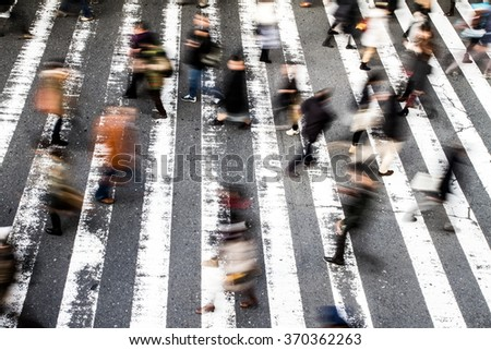 View from above of a crowd of pedestrians on a zebra crossing with motion blur to the walking people and focus to the stripes on the asphalt