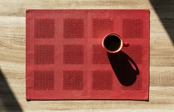 View from above of a cup of coffee with sunlight on a red placemat