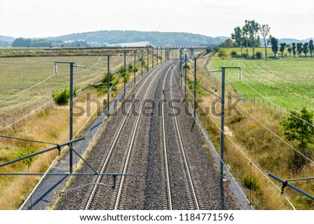 View from above of a french high-speed railway track with overhead line equipment, made of posts, catenaries, wires and power lines to supply bullet trains.