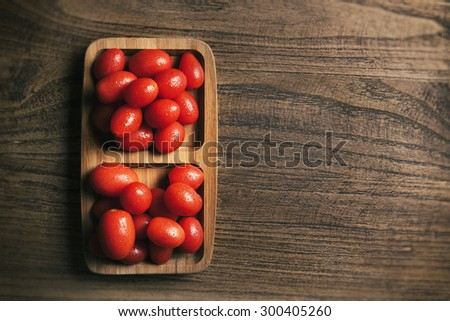 View from above of baby tomato on wood texture table