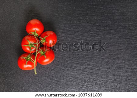 view from above of beautiful red tomatoes on black slate background with place for text, close up #1037611609