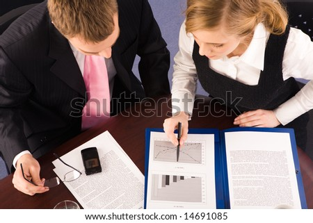 View from above of business partners sitting at table and working with documents