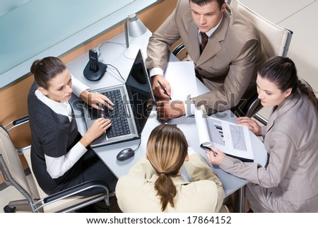 View from above of business team working at table in the office - stock photo