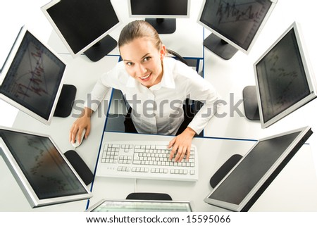 View from above of businesswoman sitting at desk with several computers around and looking upwards at camera