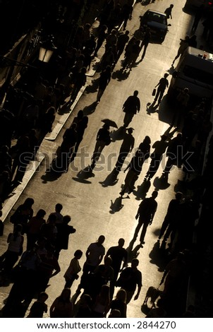 view from above of busy street with people walking silhouetted against golden light in rome italy