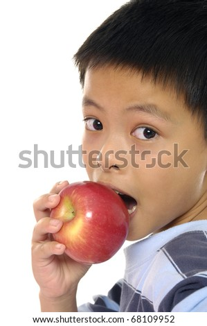View from above of cute schoolboy with and apple looking at camera