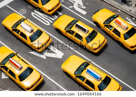 View from above of fleet of yellow taxi cabs driving down the street of Broadway in New York City