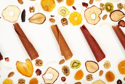 View from above of fruit lozenge different colors and almonds, orange, dried apricot, raisins, walnuts, dried apples and kiwi on white background. Concept of healthy assorted dried fruit for snacks.