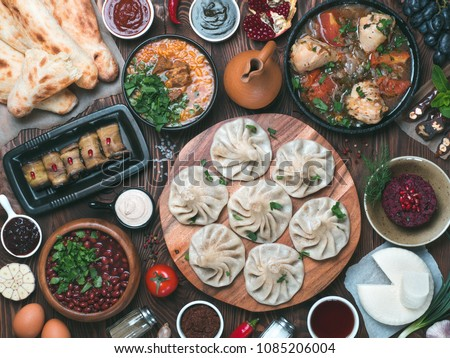 View from above of georgian cuisine on brown wooden table. Traditional georgian cuisine and food - khinkali, kharcho, chahokhbili, phali, lobio and local sauces - tkemali, satsebeli, adzhika. Top view