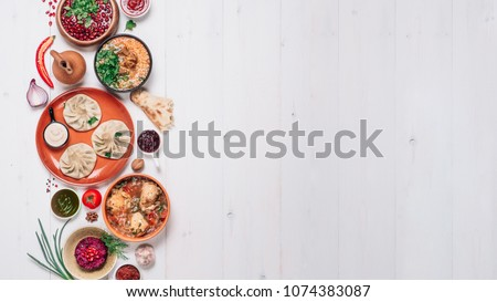 View from above of georgian cuisine on white wooden table. Banner traditional georgian food - khinkali, kharcho, chahokhbili, phali, lobio and local sauces. Top view. Copy space for text