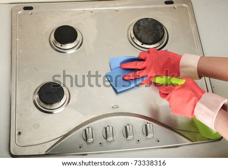 view from above of gloves cleaning a dirty inox gas cooker