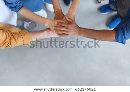View from above of group of people keeping their hands in pile expressing social friendship, unity, agreement and support. Five people of different sexes collaborating showing their strength #662176021