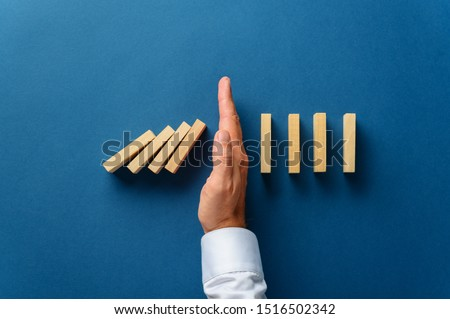 View from above of male hand interfering collapsing dominos in a conceptual image of business crisis management. Over navy blue background.