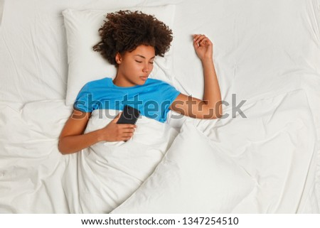 View from above of restful black young woman sleeps with smart phone, wears blue t shirt, asleep while messaging with friend, lies in comfortable bed at home or hotel, enjoys peaceful atmosphere #1347254510