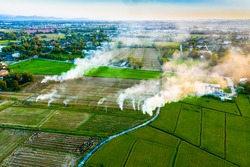 View from above of rice fields with small fire burning spots and smoke of the countryside in a blur background of town and village from afar in a evening of Chiengmai, Thailand