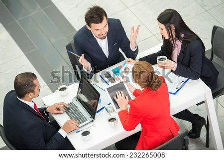 View from above of several business people are planning work around table.