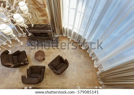 View from above of  stylish living room with fireplace and armchairs around. Interior in brown, beige and golden colors with elements of wood and dark granite. Room with big windows. #579085141