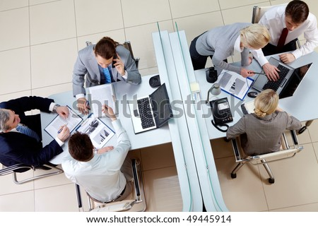 View from above of two business teams working separated by border in office