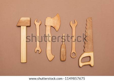 view from above on a wooden hand-made set with tools for the child. A wooden hammer, a saw, a wrench, a screwdriver, an ax are toys for a boy. flat lay